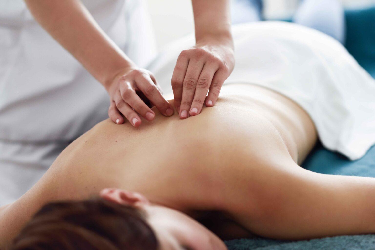 Frau liegt auf einer Liege und bekommt eine medezinische Massage