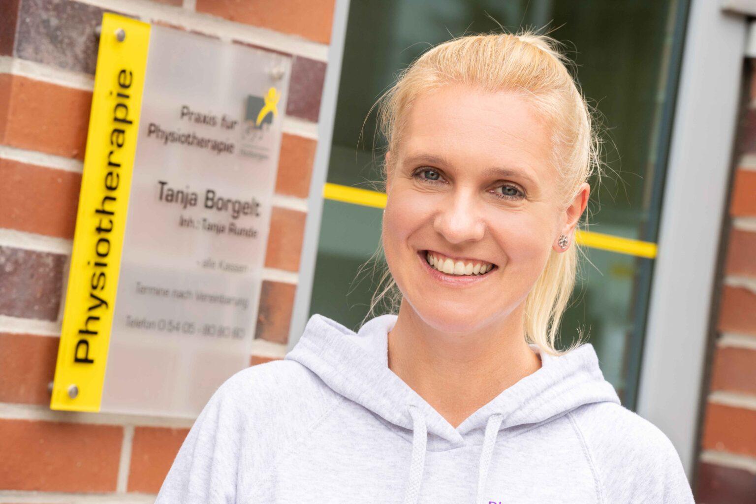 Tanja Rude vor ihrem Praxisschild