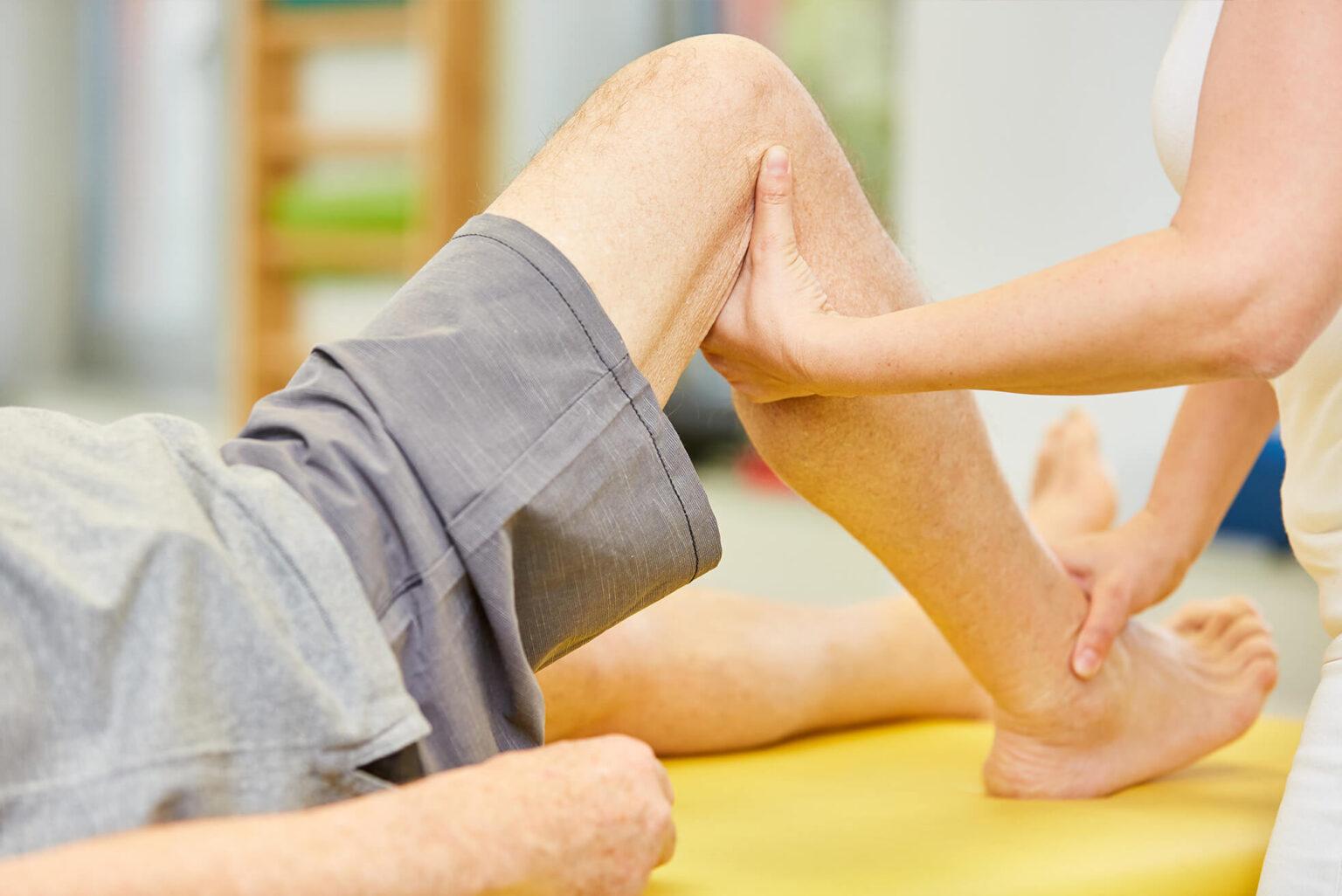 Mann liegt auf der Liege und Frau behandelt das Bein